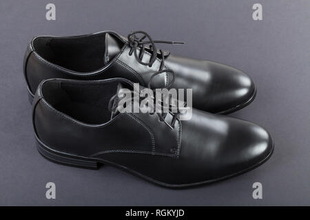 Close up picture of mens footwear. Black leather elegant shoes on grey background - Stock Photo