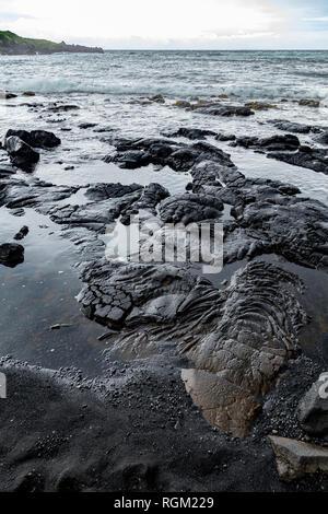 Solified lava on the shoreline of Black Sand Beach/Punaluu Beach on the Big Island of Hawaii. - Stock Photo