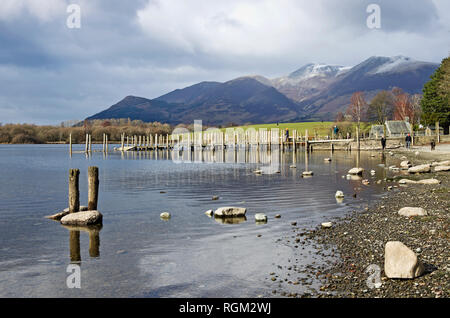 Visitors by Derwentwater lake shore and on wooden jetties by old boat house, winter, snow capped Skiddaw rising behind, Lake District Cumbria, England