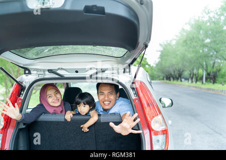 mother, father, and his daughter inside a car look out from back windows - Stock Photo