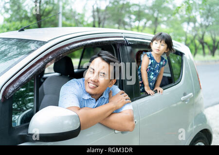 portrait father and his daughter looks out from a car windows - Stock Photo