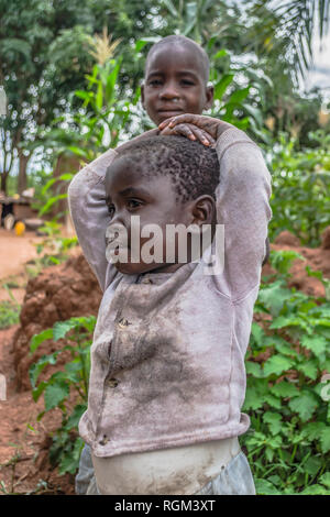 Malange / Angola - 12 08 2018 : Portrait of an Angolan child, with very expressive face, with her brother on background - Stock Photo