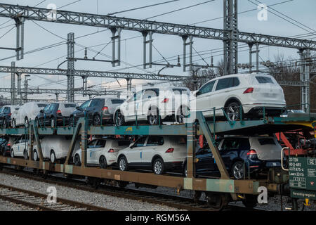 New Volkswagen cars on a freight train at train station, Slovenia - Stock Photo