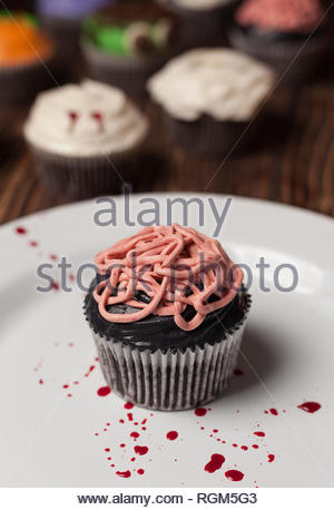 Halloween chocolate cupcake topped with black frosting and decorated with raspberry, simulates intestines, captured on white plate. - Stock Photo