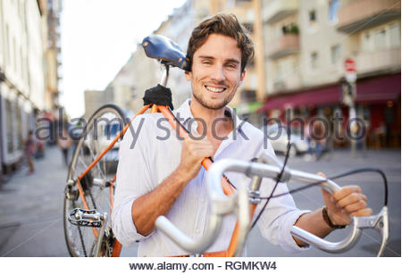 Portrait of smiling young man carrying his racing cycle on shoulder in the city - Stock Photo