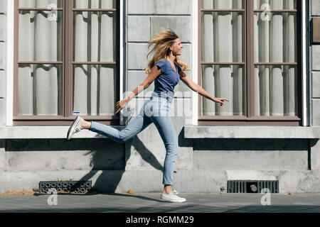 Netherlands, Maastricht, happy blond young woman running along building in the city - Stock Photo