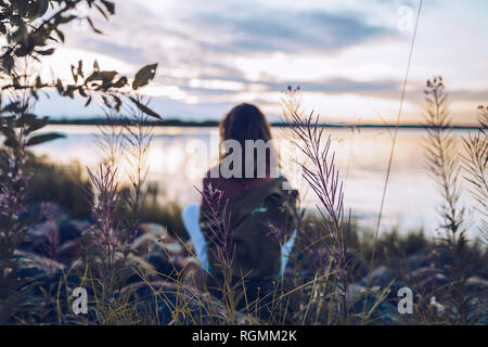 Young woman sitting at lake Inari, looking at view, Finland - Stock Photo