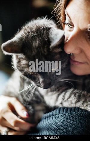 Woman hugging her grey tabby cat