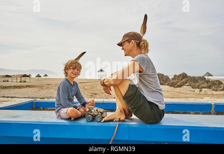 Chile, Arica, happy mother sitting with son on wall on the beach - Stock Photo
