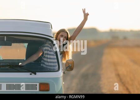 Excited young woman making victory hand sign out of camper van window in rural landscape - Stock Photo