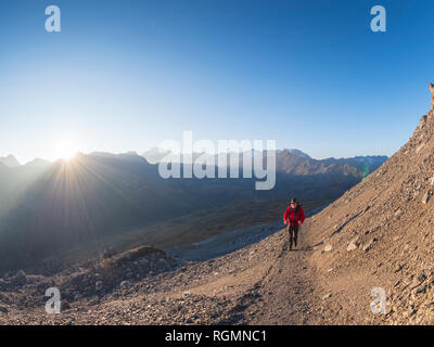 Border region Italy Switzerland, senior man hiking in mountain landscape at Piz Umbrail - Stock Photo