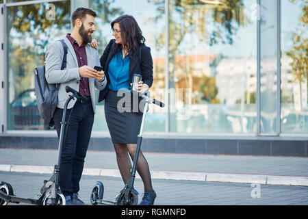 Smiling businessman and businesswoman with scooters talking on pavement - Stock Photo
