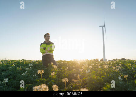 Engineer standing in a field at a wind turbine - Stock Photo