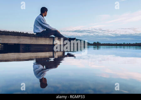 Young man sitting at lake Inari, looking at view, Finland - Stock Photo