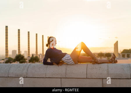 Spain, Barcelona, Montjuic, young woman lying on a wall at sunset - Stock Photo