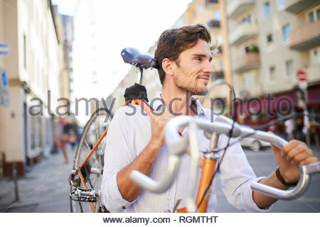 Content young man carrying his racing cycle on shoulder in the city - Stock Photo