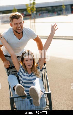 Carefree young man pushing girlfriend in a shopping cart