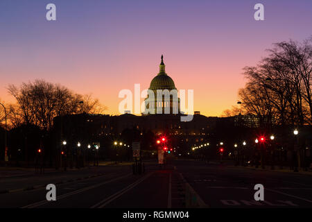A view on US Capitol from Pennsylvania avenue at dawn in Washington DC, USA. Beautiful winter sunrise with clear skies. - Stock Photo