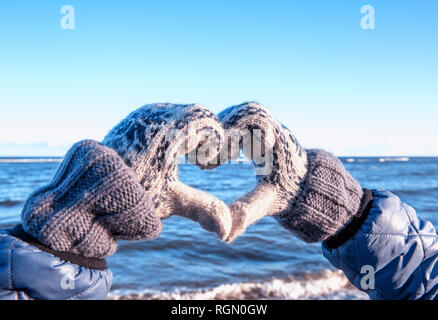 Winter gloves heart symbol shaped lifestyle in the snow against the background of Baltic sea. - Stock Photo