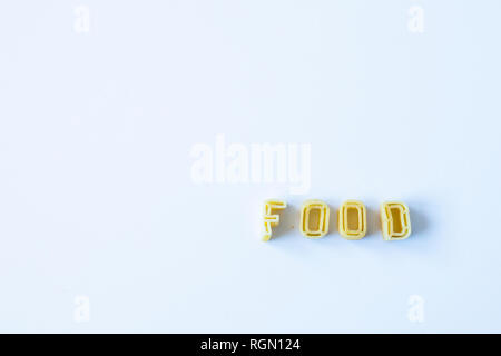 The word 'food' composed with real pasta letters on a white surface with natural light. Background with copy space on the left side. - Stock Photo