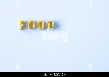 The word 'food' composed with real pasta letters on a white surface with natural light. Background with copy space on the right side. - Stock Photo