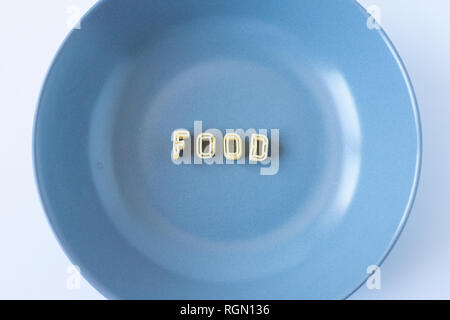 The word 'food' composed with real pasta letters in a blue dish. - Stock Photo