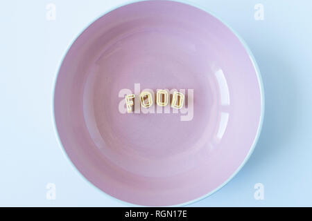 The word 'food' composed with real pasta letters in a pink dish. - Stock Photo