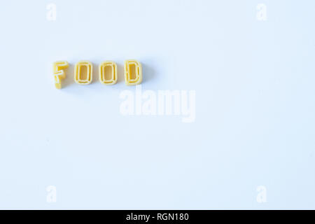 The word 'food' composed with real pasta letters on a white surface. Background with copy space on the right side. - Stock Photo
