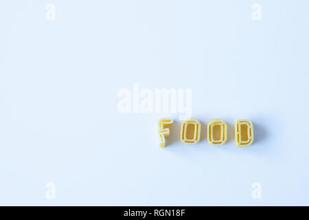The word 'food' composed with real pasta letters on a white surface. Background with copy space on the left side. - Stock Photo