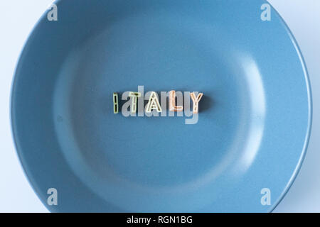 The word 'Italy' composed with real pasta letters in the italian flag colors in a blue dish. - Stock Photo
