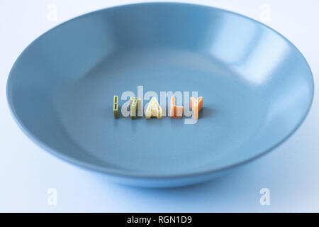 The word 'Italy' composed with real pasta letters in the italian flag colors in a blue dish.  Side view. - Stock Photo