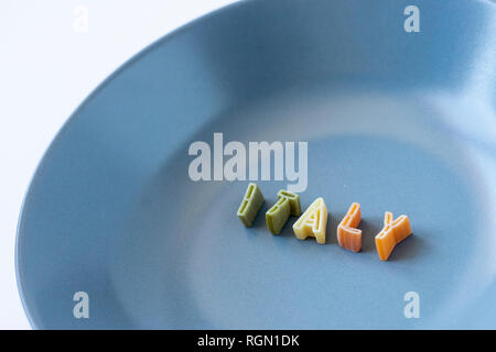 The word 'Italy' composed with real pasta letters in the italian flag colors in a blue dish. Background with copy space on the left. - Stock Photo
