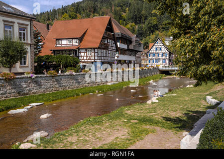 river Schiltach in the town Schiltach, Black Forest, Germany, half timbered houses at the riverside, also Kinzig valley, people relax on the bank - Stock Photo