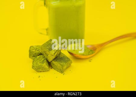 Green tea latte with ice in mason jar and straw and spoon with powder matcha and candy made of matcha on yellow background. Homemade Iced Matcha Latte - Stock Photo