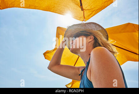 Smiling woman wearing straw hat under sunsahde in sunlight - Stock Photo