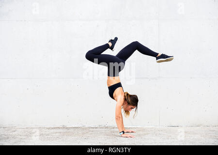 Athlete doing handstand in front of white wall - Stock Photo