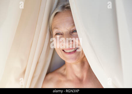 Portrait of relaxed senior woman behind curtain - Stock Photo