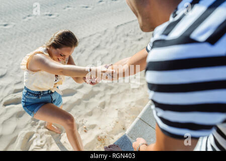 Man helping woman to climb up from the beach - Stock Photo