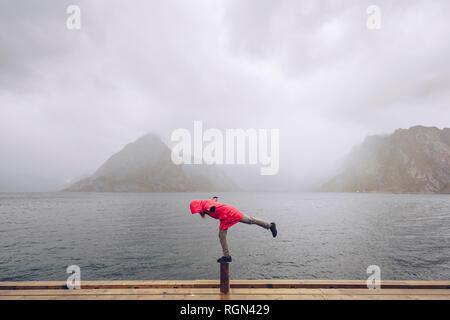 Norway, Lofoten, Hamnoy, man wearing red rain jacket balancing on wooden stake - Stock Photo