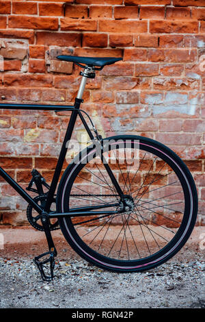 Detail of a customised commuter fixie bike at brick wall - Stock Photo