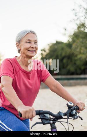 Portrait of smiling senior woman riding bicycle - Stock Photo