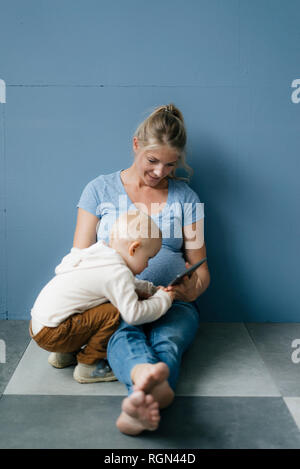 Toddler son and pregnant mother with tablet - Stock Photo