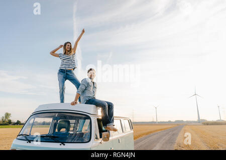 Happy couple on roof of a camper van in rural landscape - Stock Photo