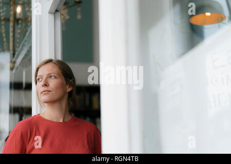 Young woman at French door in a cafe looking around - Stock Photo