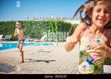 Boy with water gun splashing at girl at the poolside