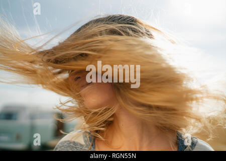 Blong young woman at camper van shaking her hair