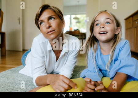 Mother and daughter lying on the floor at home watching something - Stock Photo