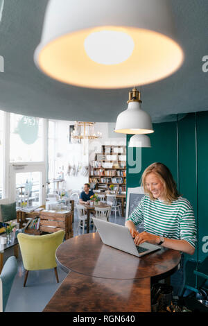 Smiling young woman using laptop in a cafe