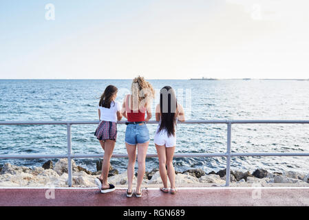 Spain, Mallorca, Palma, rear view of three young women standing at the sea - Stock Photo