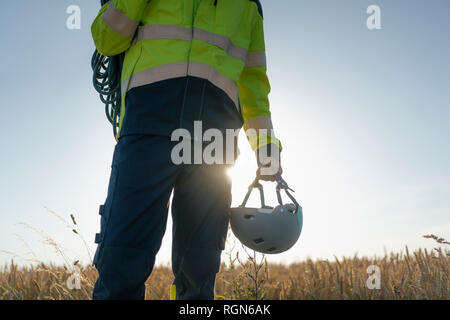 Close-up of technician in a field with climbing equipment - Stock Photo